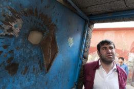 Ein Bewohner von Sur schaut auf den Einschlag eines Geschosses am Eingang einer Wohnung in der Altstadt von Diyarbakir.